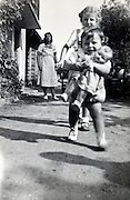 siblings running with mother in the background France 1950s