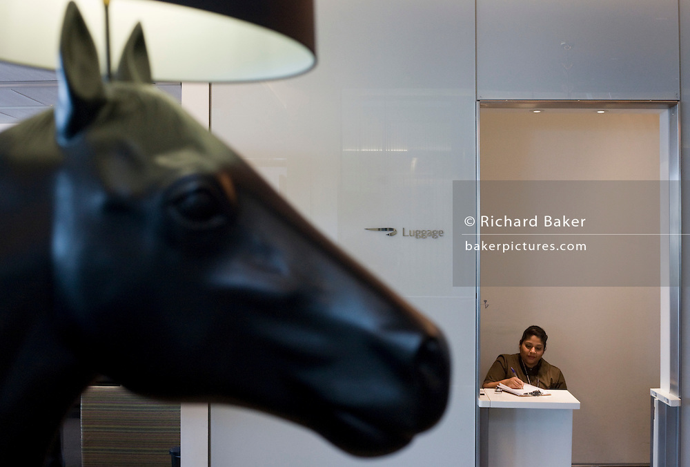 Receptionist and horse artwork in the British Airways Galleries First for First Class passengers at Heathrow airport's T5