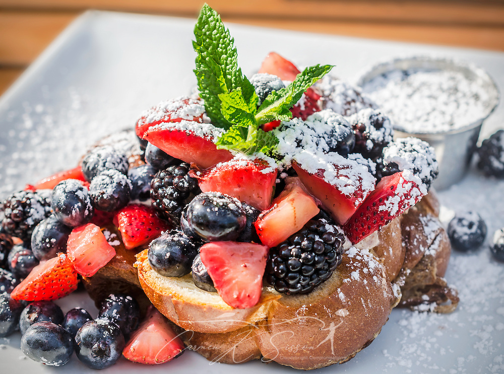 Challah French toast, stuffed with honeyed ricotta, is topped with seasonal fruit, powdered sugar, and maple syrup at Sun in My Belly Cafe, June 16, 2014, in the Kirkwood community of Atlanta, Georgia. The cafe, founded in 1996 by master chef Alison Lueker, specializes in local and seasonal food with an elegant flair. The restaurant is housed within the historic Bailey's Hardware building. (Photo by Carmen K. Sisson/Cloudybright)