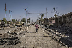 October 29, 2016 - Al Hamdaniyah, Nineveh Governorate, Iraq - A man walks down the empty street of Al Hamdaniyah as the city lay in ruins. (Credit Image: © Berci Feher via ZUMA Wire)