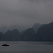 A local fisherman navigates the waters in the early morning mist in Ha Long Bay, Vietnam. The bay consists of a dense cluster of 1,969 limestone monolithic islands. Ha Long Bay, is a UNESCO World Heritage Site, and a popular tourist destination. Ha Long, Bay, Vietnam. 11th March 2012. Photo Tim Clayton