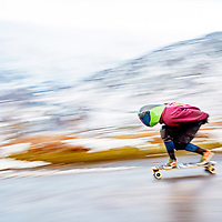 A photograph of a skateboarder travelling fast on a road in the Lake District, Cumbria, England