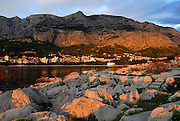 View of rocky peninsula in late afternoon sun, with town of Makarska and the Biokovo National Park, part of the Dinaric Alps, in the background. Makarska, Croatia