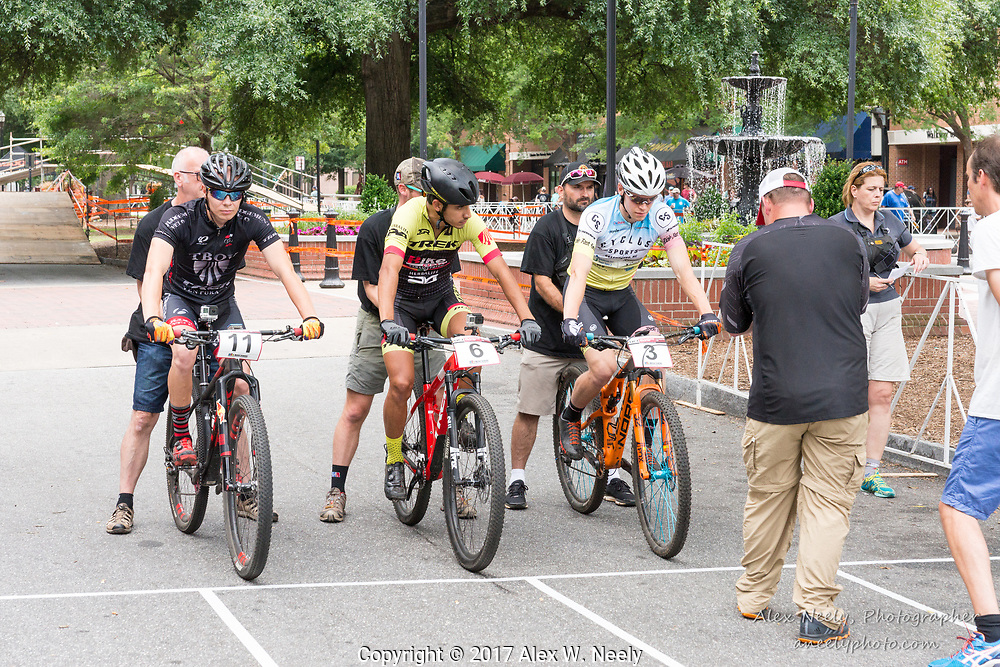 As the videographer finishes shooting closeups, Seth Kemp (#3 USA), Daniel Castillo Noyola (#6 MEX) and Jarno Trey (#11 EST) wait for the start of the 4th heat of the quarter finals during Round 2 of the 2017 UCI MTB Eliminator World Cup held in Columbus, GA, USA on June 4, 2017.