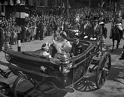 King George VI and Queen Elizabeth smile as, with their younger daughter, Princess Margaret, they return in the State Landau from the Service of Thanksgiving at St Paul's Cathedral. The picture was taken as the procession passed along the Victoria Embankment.