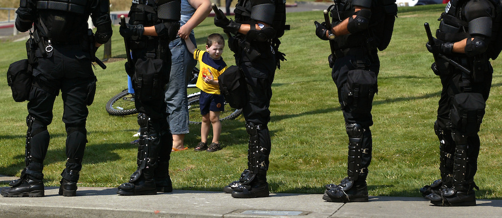 Riot police begin to assemble along the motorcade route just before the arrival of President George W. Bush. He made a campaign stop at Southridge High School in Beaverton....