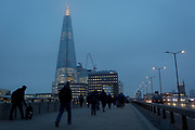 Commuters walk southwards over London Bridge towards the Shard skyscraper on a winter's mid-afternoon, on 23rd November 2018, in London, England.