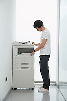 Man using copy machine in hallway