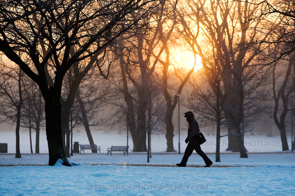 EDINBURGH, UK - 8th January 2010:  A man walks to work through Edinburgh meadows in early morning sunrise as UK temperatures remain at sub-zero after the Met Office recorded the winter's coldest day yet..Temperatures  plunged to -22.3C in the Highlands.. (Photograph: Michael Hughes/MAVERICK)