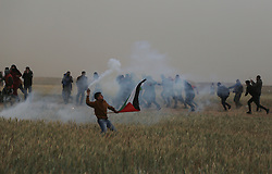 March 30, 2019 - Gaza, khan younis, Palestine - A protester with a flag seen throwing back a tear gas can fired by Israeli forces during clashes..Palestinian protesters clashed with Israeli forces in the wake of a million-strong protest on the ground, demanding the right of return to their homeland on the border between Israel and Gaza in Khan Yunis in the southern Gaza Strip. The Health Ministry in the Hamas-run sector said three Palestinians were killed by Israeli fire during the clashes. (Credit Image: © Yousef Masoud/SOPA Images via ZUMA Wire)