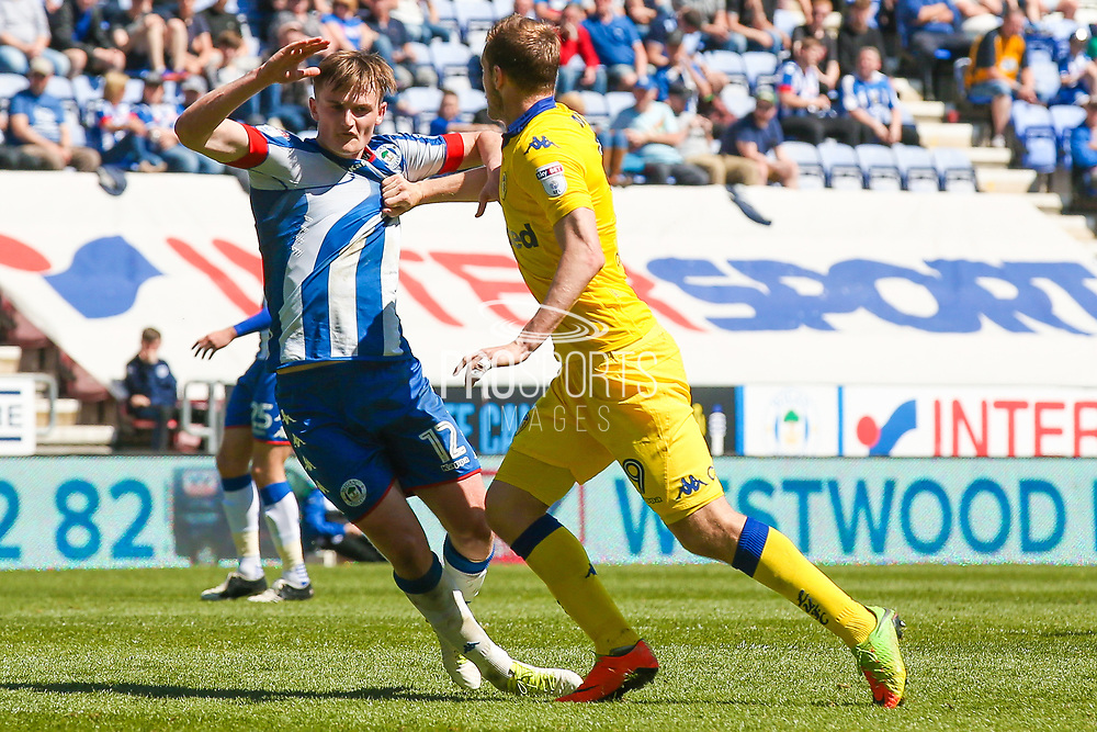 Wigan Athletic  defender, on loan from Everton, Callum Connolly (12) tussles with Leeds United forward Chris Wood (9)  during the EFL Sky Bet Championship match between Wigan Athletic and Leeds United at the DW Stadium, Wigan, England on 7 May 2017. Photo by Simon Davies.