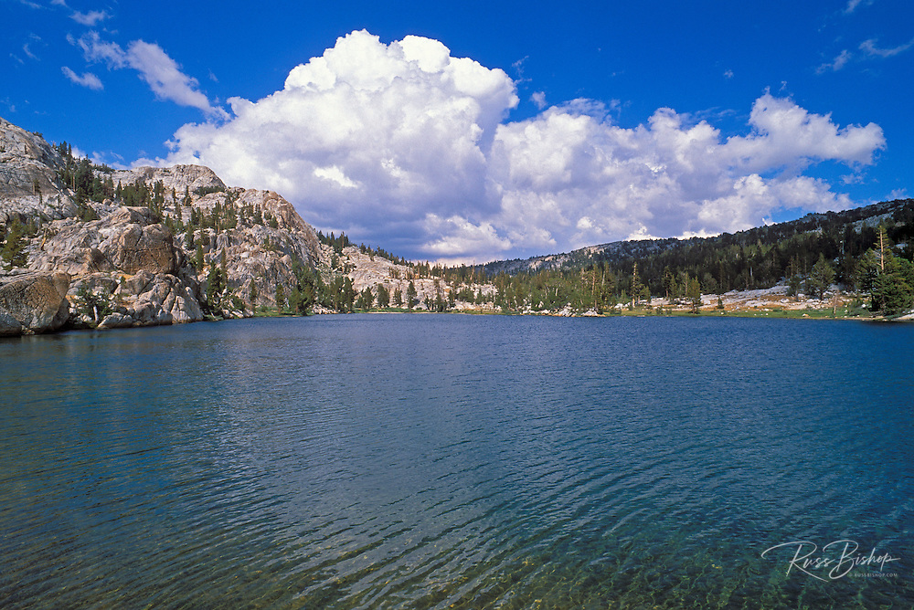 Blue sky and clouds over Boothe Lake in the Cathedral Range, Sierra Nevada Mountains, Yosemite National Park, California.