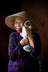 Portrait of an old vietnamese woman in Hoi An, Vietnam, Asia. She carries a cute little dog. Portrait d'une vietnamienne agée qui tient un petit chien dans ses bras.