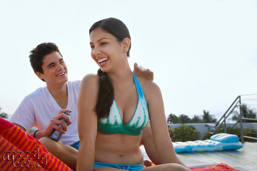 Teenage boy (16-17) applying sunscreen lotion to girl's back