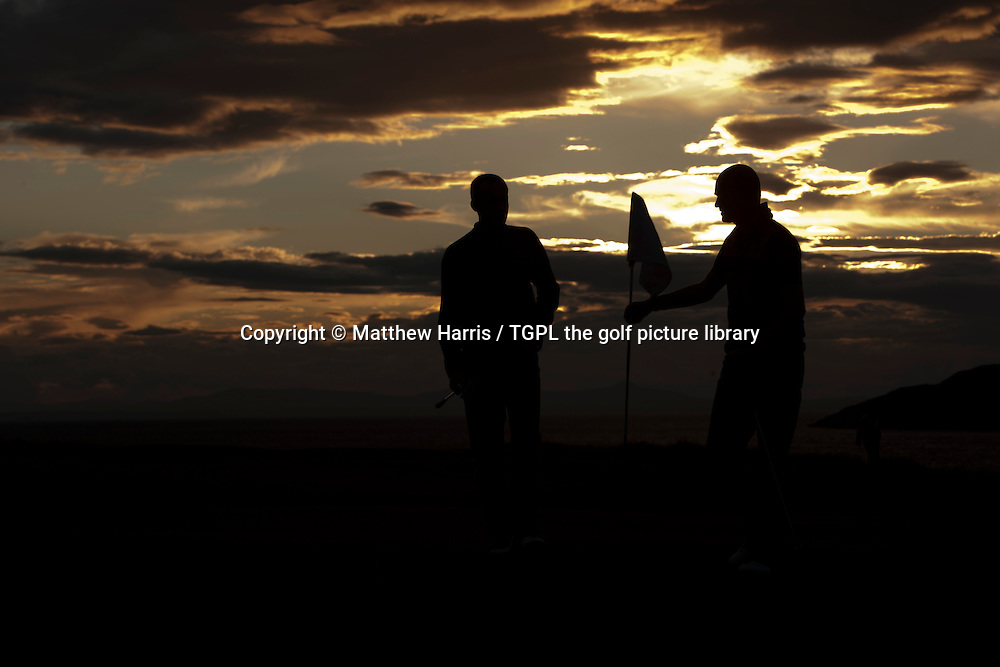 Silhouette of two golfer's finishing their round at sunset during summer at The Glen,North Berwick,East Lothian,Scotland.