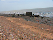Eroded pill box on beach. Rapid coastal erosion at East Lane, Bawdsey, Suffolk, England. Soft crag cliffs are easily eroded, dark underlying London clay is exposed.