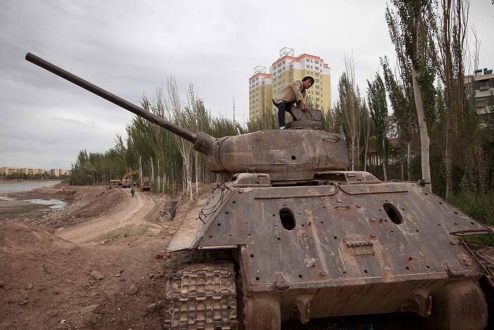 A man lifting the hatch of a wrecked tank in front of a new residential development. Kashgar (Kashi in Chinese) is in Xinjiang province in the extreme west of China at the edge of the Taklamakan Desert. It has a long history as an important trading center at the junction of the two branches of the ancient silk road. The Old town of Kashgar is one of the best-preserved examples of a traditional Islamic cities in Central Asia but is today under constant threat of being razed by plans of modernization initiated by the Chinese government.