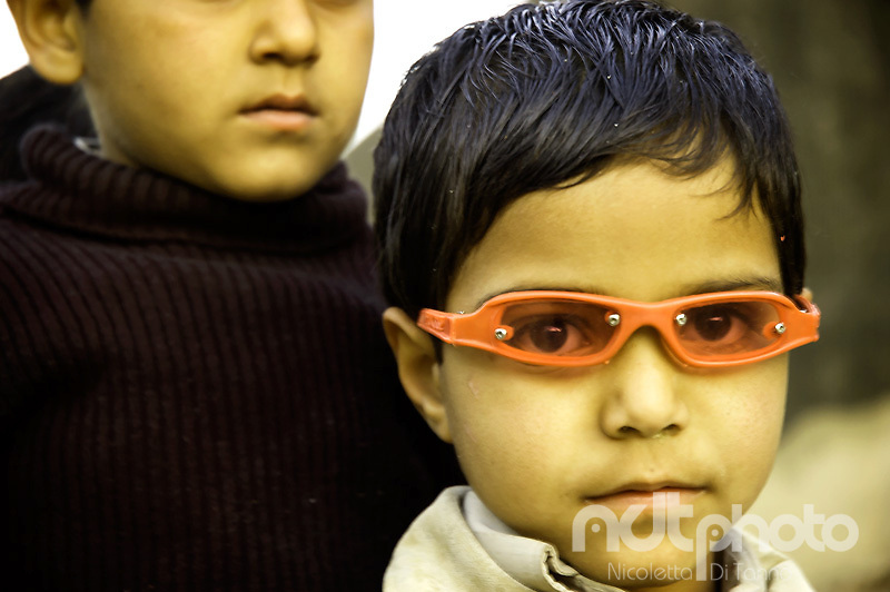 A young boy looks through his fashion red sunglasses.Rajasthan, India
