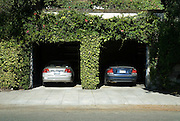 Berkeley, CA, May, 2008-Two cars parked in side by side garages.