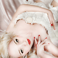 Delicate blonde girl in white corset laying down on silk sheets