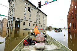 May 2, 2019 - Davenport, Iowa, U.S. - Ryan Lincoln maneuvers his jon boat through flood water at the intersection of Pershing Ave and E 2nd St. Thursday. Lincoln's employer Hahn Ready Mix allowed him to take time off from work to volunteer ferrying people back and forth to their apartments and businesses affected by the flooding  in downtown Davenport. (Credit Image: © Kevin E. Schmidt/Quad-City Times via ZUMA Wire)