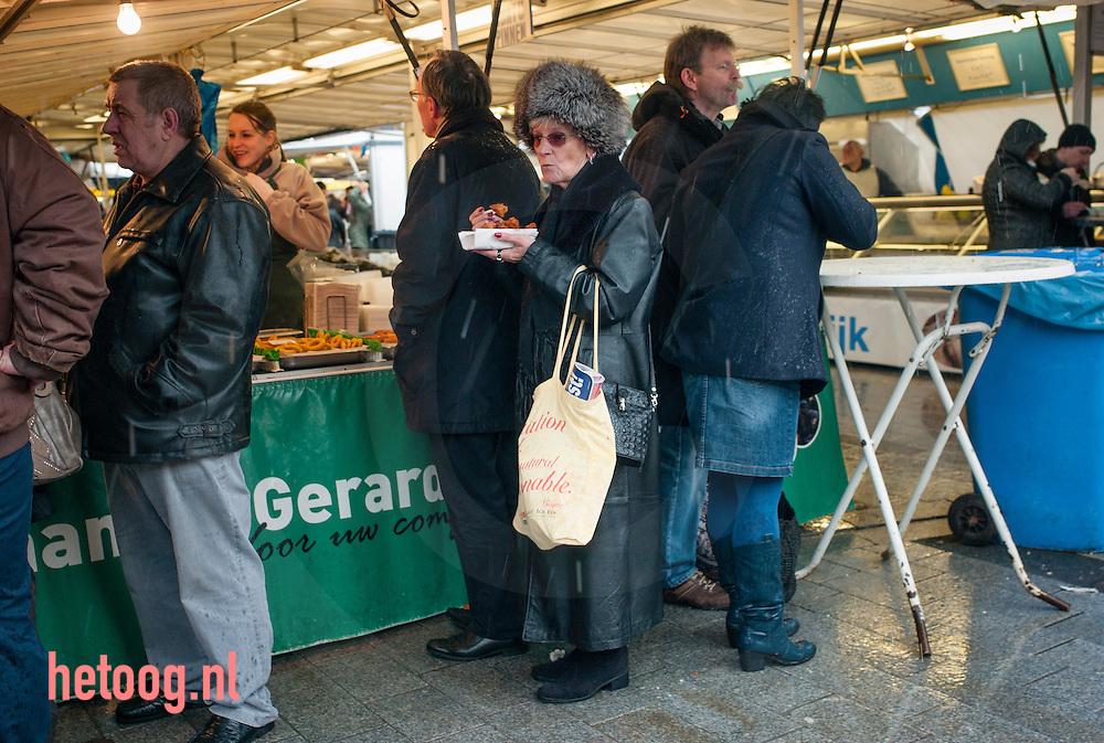 nederland, enschede 21feb205 Duitse dame  eet een gebakken vis  op de zaterdagse warenmarkt in Enschede