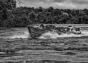 Fleuve Oyapock, Ilha Bela, 2015.<br /> <br /> Pirogue &laquo; clandestine &raquo; de garimpeiros &agrave; proximit&eacute; d&rsquo;Ilha Bela. Chaque matin, les pirogues partent d&rsquo;Oiapoque pour ravitailler ce &laquo; village fronti&egrave;re &raquo;, base arri&egrave;re de l&rsquo;orpaillage clandestin sur la rive br&eacute;silienne de l&rsquo;Oyapock, &agrave; proximit&eacute; de Camopi.<br /> <br /> La r&eacute;gion connait depuis les ann&eacute;es 1990 sa seconde ru&eacute;e vers l&rsquo;or. Dans un premier temps, le fleuve est exploit&eacute; par des barges, des pompes sont install&eacute;es sur des radeaux &agrave; la recherche de l&rsquo;or alluvionnaire. Aujourd&rsquo;hui, apr&egrave;s l&rsquo;&eacute;puisement des sables aurif&egrave;res les garimpeiros s&rsquo;int&eacute;ressent aux anciens chantiers miniers guyanais. <br /> L&rsquo;Oyapock est devenu un axe de transit de mat&eacute;riel, de ravitaillement et de main d&rsquo;&oelig;uvre clandestine. La Camopi et la Sikini, deux affluents du fleuve, constituent les voies d&rsquo;acc&egrave;s qui permettent de se rendre sur les chantiers de la r&eacute;gion mais aussi de rejoindre les bassins du Maroni et de l&rsquo;Approuague, principales zones aurif&egrave;res de Guyane.