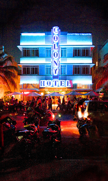 Night on Miami Beach's Ocean Drive in South Beach with motorcycles and the neon-lit, Art Deco style, Colony Hotel, designed by Henry Hohauser in 1935.