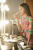 Woman stands applying makeup in dressing room mirror