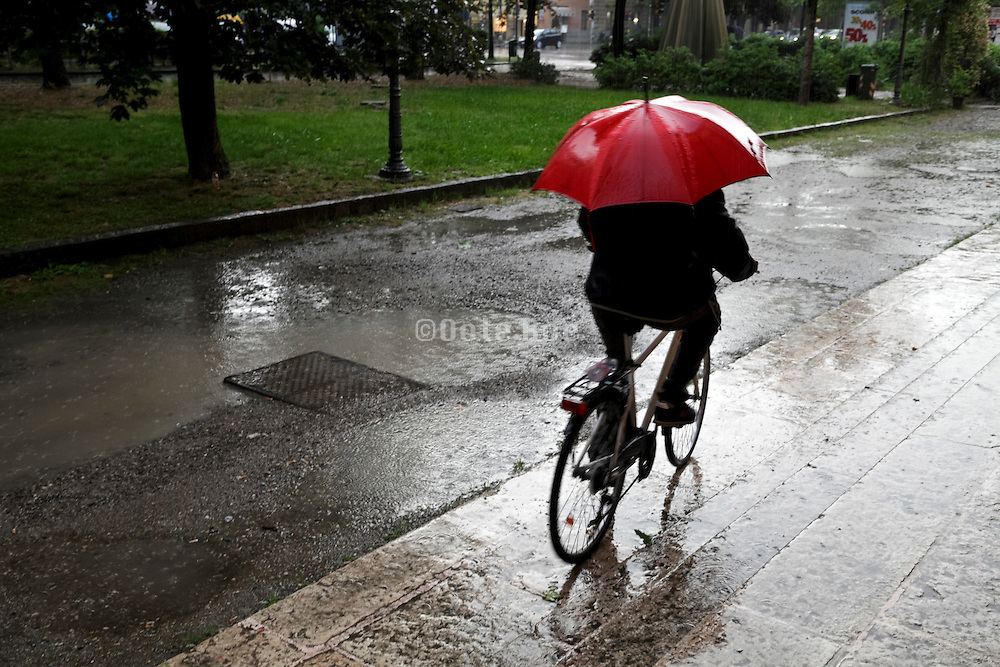 bicycling with red umbrella during a heavy rain storm