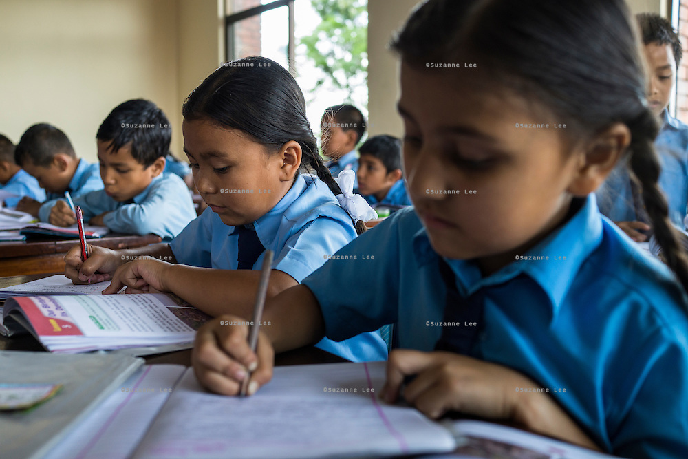 Usha (name changed, 4th from left), aged 10, studies in her classroom in SOS Children's Villages Sanothimi, Bhaktapur, Nepal on 2 July 2015. Usha's entire family perished when her house collapsed in the earthquake on 25th April 2015. Usha is now well integrated into her new family and school. Photo by Suzanne Lee for SOS Children's Villages