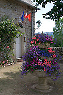 Tiers of summer flowers in a stone urn in Creysse, Dordogne, France