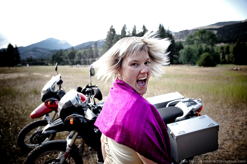 A woman in a dress with shawl turns quickly and laughs while standing near two motorcycles in a rural field in the mountains.
