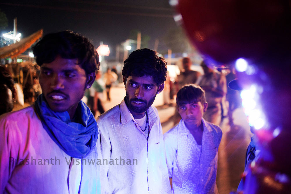 Men react as they listen to a robot predicting their future at the fair grounds in Pushkar, India, November 5, 2011.  Photographer: Prashanth Vishwanathan