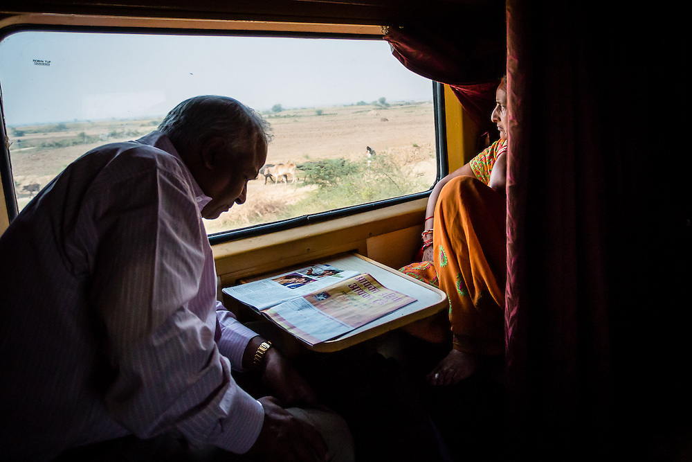 A couple travels on the train from Jaipur to Kota Junction, the man reading a magazine, and is wife looking out the window.