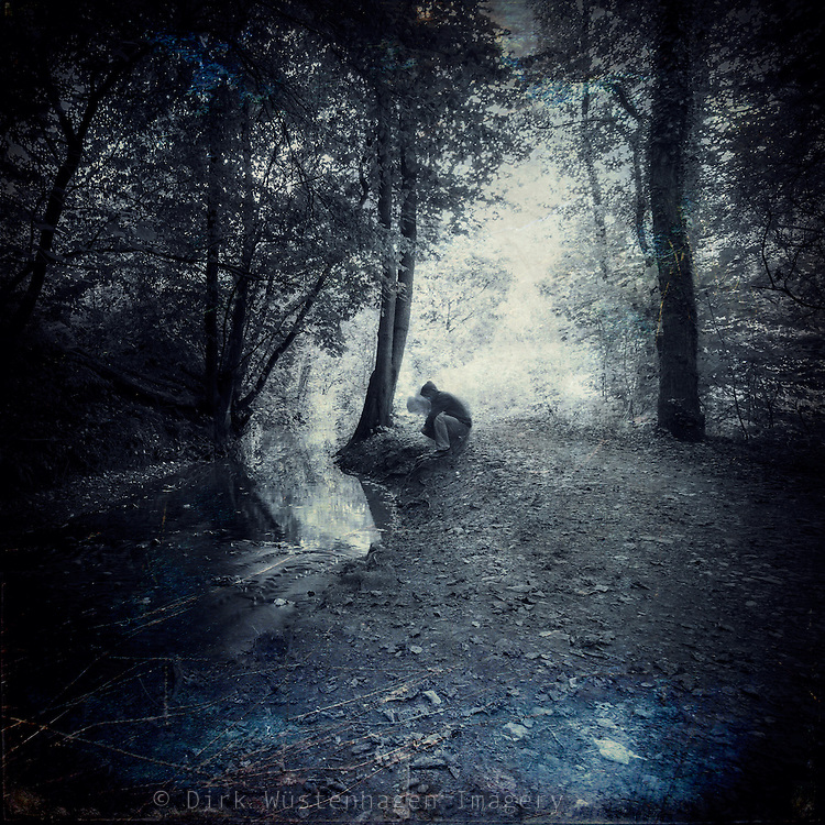 Man cowering at a slow flowing creek pondering - texturized and manipulated photograph