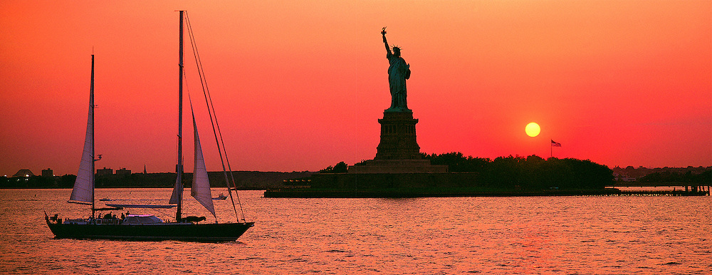 Statue Of  Liberty at Sunset with Sailboat in New York Harbor looking East