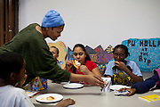 Children, including Anthony Jackson, Alexis Jackson, 11, and Brent Hucks, 10, enjoy pizza inside of the Braddock Community Center, which is in the abandoned First Presbyterian Church...The town, which is known for its steel mills, has lost the majority of its population, as well as its hospital, which was recently torn the down. Many abandoned homes line its streets.
