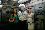 "A North Korean sailor poses for a snapshot with Chinese tourist aboard the American ship ""Pueblo"" captured by North Korea, now docked in Pyongyang, North Korea Sunday Aug. 5, 2007. The leaders of North and South Korea will meet this month for the second time since the peninsula's division after World War II, capitalizing on progress in Pyongyang's nuclear disarmament to revive their historic reconciliation.(AP Photo/Elizabeth Dalziel)"