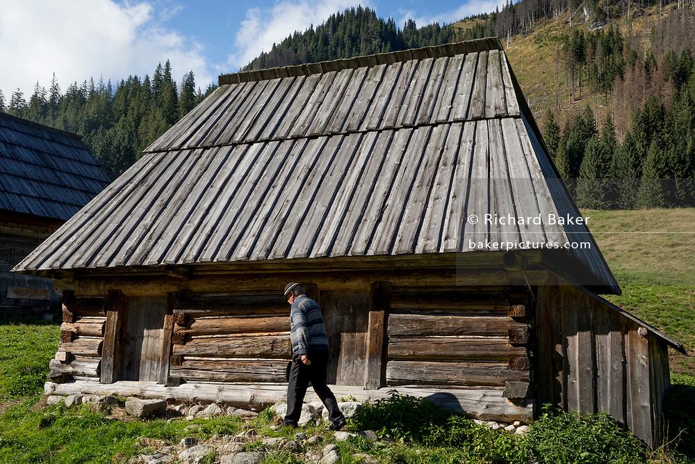 A mountain farmer walks past an agricultural hut on Polana Chocholowska a hiking route on Dolina Chocholowska in the Tatra National Park, on 17th September 2019, near Zakopane, Malopolska, Poland.
