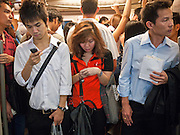 """08 JULY 2011 - BANGKOK, THAILAND: People stand in the doorway and wait for the train to leave the Siam station in the BTS or Skytrain in Bangkok, Thailand. Bangkok's """"Skytrain"""" system, officially called the BTS, cuts across the city from the Chao Phraya River to the Weekend Market.   PHOTO BY JACK KURTZ"""