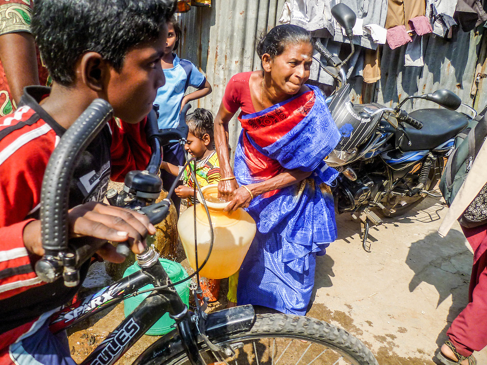 Weighing Heavily, Chennai, India by Kavya. <br /> <br /> An Indian woman fetching water in an urban slum in Chennai, India. <br /> <br /> Kavya is 11 years old and she has already found her interest in Science subjects and she would like to be an engineer in the future.