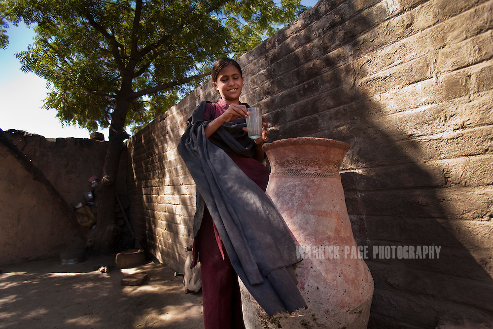 The sister of Mohammad Ali collects unclean water to drink outside their home on October 13, 2011, in Manzoorabad, Pakistan. Her brother Mohammad, was discharged from the nutrition stabilisation centre in Jamsharoo, after being admitted two months ago with severe malnutrition brought on by TB and pneumonia. According to UN reports, hundreds of thousands of children in Pakistan suffer from severe-acute-malnutrition, with 15.1% of children experiencing acute malnutrition. Child malnutrition has breached emergency levels in Pakistan's Sindh province, after monsoon floods devastated the country's poorest region for a second year. Extreme poverty, poor diet and health, exposure to disease, and inadequate sanitation and hygiene annually produce alarming levels of malnutrition amongst children, but the floods have increasingly endangered an already vulnerable population. (Photo by Warrick Page)
