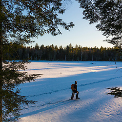 A man snowshoes across a frozen beaver pond on newly conserved land in Epping, New Hampshire.