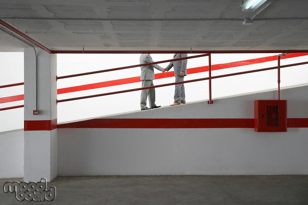 Two businessmen shaking hands on ramp in parking garage