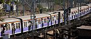 Commuter train of Western Railway approaching Mahalaxmi Station on the Mumbai Suburban Railway while builder at work, India