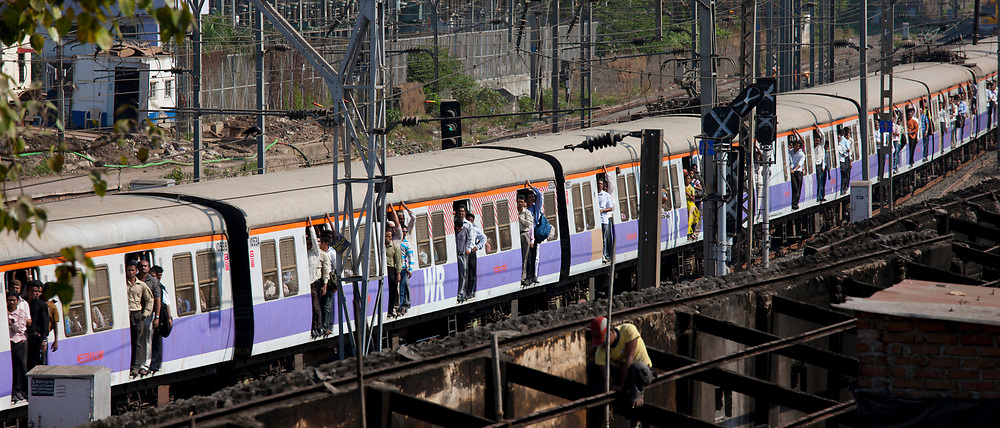 Commuter train of Western Railway approaching Mahalaxmi Station on the Mumbai Suburban Railway while builder at work, India
