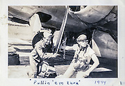 "Lt. Swenson and ""Babe"" (a friend) pulling the radial engine propellers through several rotations to circulate the oil prior to startup."