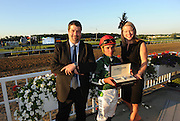 Tonalist jockey Joel Rosario, working back to back races, is presented his Longines timepiece for winning the Belmont Stakes, by Jennifer Judkins, right, and Sebastien Zbinden, left, both of Longines, after Tonalist won the146th Belmont Stakes, Saturday, June 7, 2014, at Belmont Park in New York.  Longines, the Swiss watchmaker known for its elegant timepieces, is the Official Watch and Timekeeper of the 146th running of the Belmont Stakes. (Photo by Diane Bondareff/Invision for Longines/AP Images)