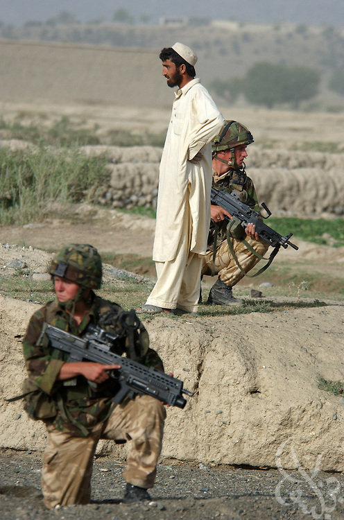 A local Afghan watches as British Royal Marines of 45 Commando undertake an eagle vehicle check point (VCP) operation as part of the ongoing Operation Buzzard July 8, 2002 in southeastern Afghanistan. During VCPs, small groups of marines are dropped quickly by helicopters to search random vehicles on dirt roads and trails near the Pakistan-Afghanistan border to deny al Qaeda and Taliban fighters freedom of movement across the region.